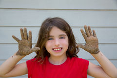 Happy kid girl playing with mud with dirty hands smiling Stock Photos