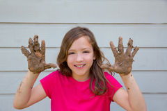 Happy kid girl playing with mud with dirty hands smiling Stock Photography