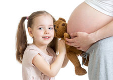 Happy kid girl playing with pregnant mother Royalty Free Stock Images