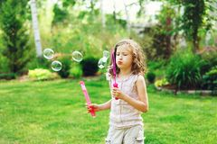 Happy kid girl playing with soap bubbles in summer. Garden royalty free stock image