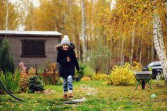 Happy kid girl running in late autumn garden. With wooden shed on background stock photo