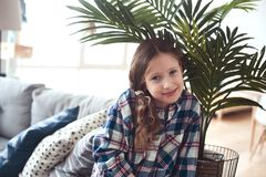 Happy kid girl sitting on couch near tropical house plant. At home stock images