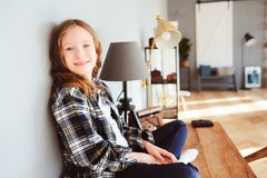 Happy kid girl sitting on table at home and wring. Learning lessons, successfull education Stock Images