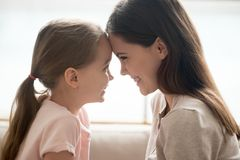 Happy kid girl and smiling mother touching foreheads, side view royalty free stock photos