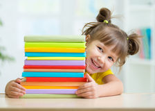 Happy kid girl with a stack of books. Playful kid girl with a stack of books at home royalty free stock images