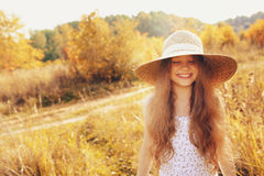 Happy kid girl in straw having fun outdoor on summer sunny field Stock Images