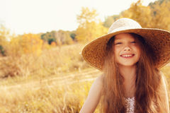 Happy kid girl in straw having fun outdoor on summer sunny field Royalty Free Stock Photos