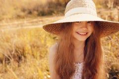 Happy kid girl in straw having fun outdoor on summer sunny field Stock Photo