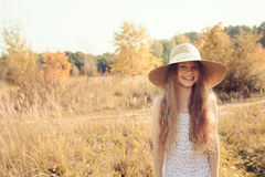 Happy kid girl in straw having fun on summer field Stock Image