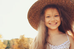 Happy kid girl in straw having fun on summer field Royalty Free Stock Photography