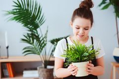 Happy kid girl taking care of houseplants at home, dressed in stylish black and white outfit. Modern scandinavian interior with tropical plants on background royalty free stock photos