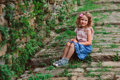 Happy kid girl on the walk in old city at stone wall Stock Photos