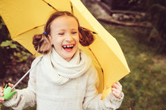 Happy kid girl in warm knitted sweater playing and hiding under umbrella on the walk in rainy autumn day in park Stock Photography