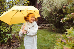 Happy kid girl in warm knitted sweater playing and hiding under umbrella on the walk in rainy autumn day in park Royalty Free Stock Photography