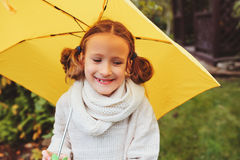 Happy kid girl in warm knitted sweater playing and hiding under umbrella on the walk in rainy autumn day in park Royalty Free Stock Images