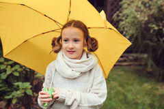 Happy kid girl in warm knitted sweater playing and hiding under umbrella on the walk in rainy autumn day in park Royalty Free Stock Photos