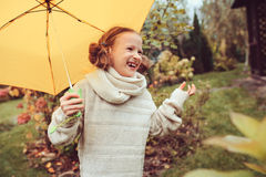 Happy kid girl in warm knitted sweater playing and hiding under umbrella on the walk in rainy autumn day in park Royalty Free Stock Image