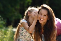 Happy kid girl whispering the secret to her laughing young mother in ear with fun face on summer green tree and grass background. royalty free stock photography
