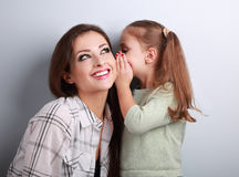 Happy kid girl whispering the secret to her smiling mother in ea Royalty Free Stock Images