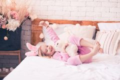 Funny kid girl in room. Happy kid girl 5-6 year old having fun with teddy bear in bed with thumb up closeup stock photos