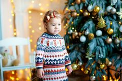 Happy kid girl 2 year old laughing in room over christmas tree. Wearing stylish knitted sweater. Looking at camera royalty free stock photos