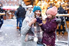 Happy kid girl and young beautiful woman with cup of steaming hot chocolate and mulled wine. Adorable child and stock photo