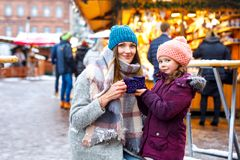 Happy kid girl and young beautiful woman with cup of steaming hot chocolate and mulled wine. Adorable child and stock images