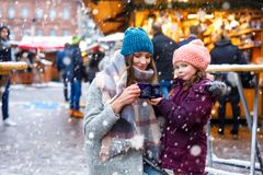 Happy kid girl and young beautiful woman with cup of steaming hot chocolate and mulled wine. Adorable child and. Happy kid girl and young beautiful women with stock photos