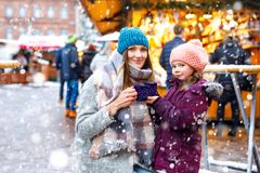 Happy kid girl and young beautiful woman with cup of steaming hot chocolate and mulled wine. Adorable child and stock photography
