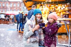Young woman and cute kid girl with cup of steaming hot chocolate or children punch. Happy kid girl and young beautiful women with cup of steaming hot chocolate royalty free stock image