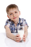 Happy kid with a glass of milk leaning on the table Royalty Free Stock Photo