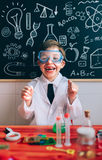 Happy kid with glasses laughing behind of experiments table Stock Photo
