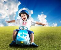 Happy kid on green meadow Stock Images