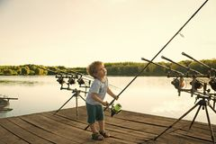 Happy kid having fun. Angling child with fishing rod on wooden pier. Angling, fishing, activity, adventure, hobby, sport Stock Photo