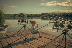 Happy kid having fun. Angling, fishing, activity, adventure, hobby, sport. Angling child with fishing rod on wooden pier Stock Photos