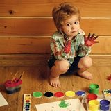 Happy kid having fun. Arts and crafts. Boy painter painting on wooden floor. Imagination, creativity and freedom concept. Child with colored hands, gouache royalty free stock photos