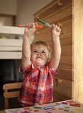Happy kid having fun. Kid or blonde happy boy paint with felt pen. Royalty Free Stock Image