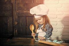 Happy kid having fun. Boy cook in chef hat and apron in kitchen. Child using spoon, rolling pin and cutters on table. Homemade cooking and baking. Playing and royalty free stock photos