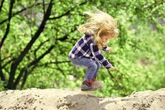 Happy kid having fun. Child bounce on sand in spring or summer park. Boy jump on pile of sand on idyllic day. Kid with long blond hair in shirt, jeans outdoor Stock Photos