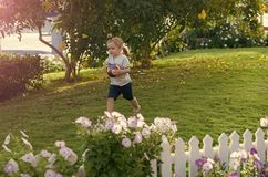 Happy kid having fun. Child play with ball on green grass on idyllic day royalty free stock photo