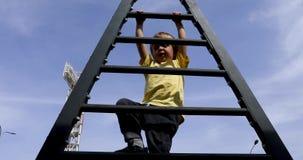 Happy kid having fun climbing on ladder. View from below stock video
