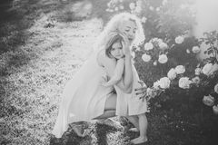 Happy kid having fun. Family love and care. Woman with girl child at blossoming rose flowers. Mothers day concept. Mom cuddling daughter on green grass on Royalty Free Stock Photos