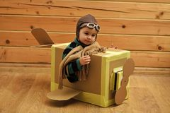 Happy kid having fun. Kid boy playing pilot flying a cardboard box in children room royalty free stock images