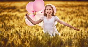 Girl running on cereal field. Happy kid is having fun on nature in the summer. Child is laughing and playing on meadow at sunset background. Girl with air stock photography