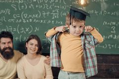 Happy kid having fun. Parents listening their son, chalkboard on background. Boy presenting his knowledge to mom and dad. Happy kid having fun. Boy presenting stock image