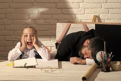 Happy kid having fun. Schoolgirl with shocked face and her sleeping tutor. Girl and teacher in classroom on white brick background. Kid and men sit and lie by Stock Photography