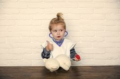 Happy kid having fun. Kid veterinarian doctor with thumbs up gesture diagnose teddy bear. With stethoscope on white wall. Health, healthcare, medicine. Future royalty free stock photos