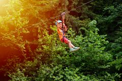 Happy kid with helmet and harness on zip line between trees.  royalty free stock photo