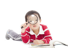 Happy kid is holding magnifying glass to explore Stock Image