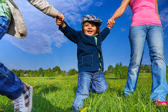 Happy kid holding parents hands in park. While walking in summer stock photography